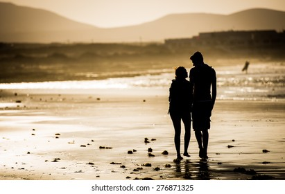 Silhouette of the loving couple, walking on the beach