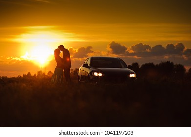 Silhouette of loving couple watching beautiful bright romantic sunset, standing leaning against blue sport car. The fields around them. The young man shows to his girlfriend evening sun
