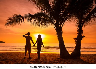 Silhouette loving couple - young man and beautiful woman at sunset on background colorful sky and reflection in water