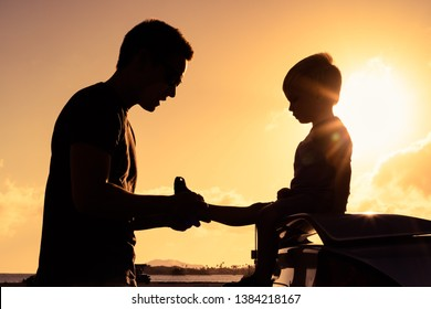 Silhouette of loving father putting his little boys shoes on.