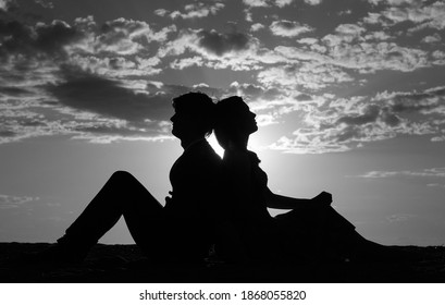 Silhouette of loving girl and guy sitting back to each other against the blue sky with clouds at sunset. Magic moments of loving hearts.Lovers in nature.Lovers silhouette.Young happy couple in love