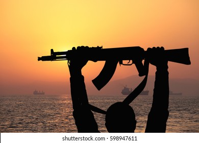 silhouette of machine gun in male hands against the backdrop of the sunset over sea