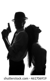 Silhouette of a mafia or gangster with a gun in his hands beautiful woman beautiful girl next to leaning against her back on a white background. Crime detective concept