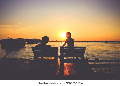 Silhouette of male and female at sunset background