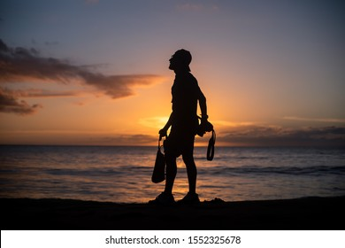 The silhouette of a male hobbyist photographer taking photos of a beautiful colorful sunset on the West Puerto Rico coast near Rincon - a popular beach among tourists year-round.