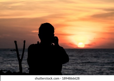 The silhouette of a male hobbyist photographer taking photos of a beautiful colorful sunset.