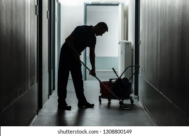 Silhouette Of A Male Janitor Cleaning Corridor