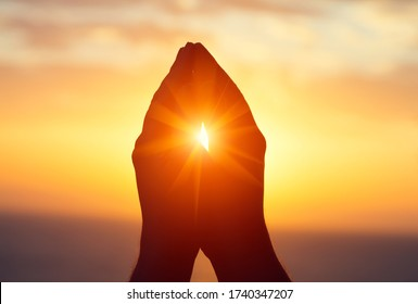 silhouette of male  raising hands praying for God's blessings at sunset or sunrise light, practicing yoga on the beach, religion, freedom and spirituality concept