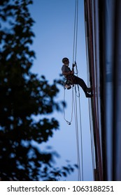 Silhouette of male rope access industry worker, wearing full safety body harness working at height, abseiling down from completed his work, in Sydney city CBD, Australia