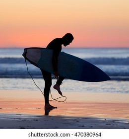 Silhouette of male surfer on the beach with the surfboard in sunset.