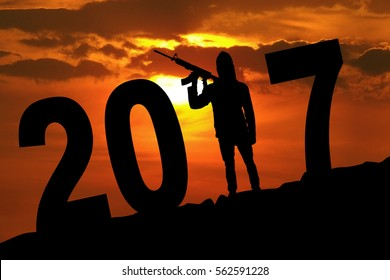 Silhouette of male terrorist carrying guns while terrorizing the new year with numbers 2017 on the hill
