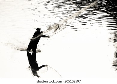 Silhouette of a male throwing a cast net to catch fish silhouette