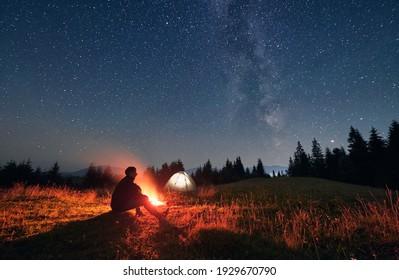 Silhouette von männlichen Reisenden sitzend nahe Lagerfeuer unter Nachthimmel mit Sternen und Milchstraße. Sternenhimmel unter grasbem Hügel mit Wanderer, Feuer und Zelten. Konzept des Reisens und des Nachtcampings.