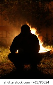silhouette of a man against a fire at night in a village