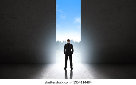 Silhouette of man against giant doorway. Space of infinite possibilities concept