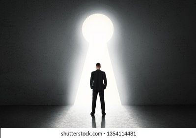 Silhouette of man against giant keyhole door. Key to everything concept