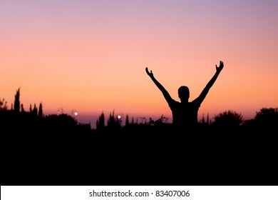 Silhouette of a man with arms raised at night