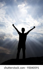 Silhouette of a man with arms stretched out to the sky