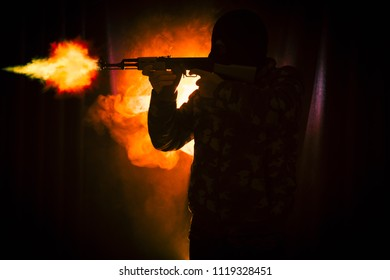 Silhouette of man with assault rifle ready to attack on dark toned foggy background or dangerous bandit in black wearing balaclava and holding gun in hand. Shooting terrorist with weapon theme decor
