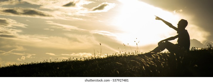 Silhouette of a man in the background sunset sky.
