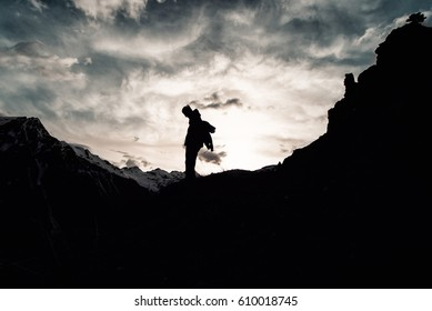 silhouette of man with a backpack in camouflage rises to the top of the mountain. A man in military clothes rises to the mountains on the way in the summer. alone