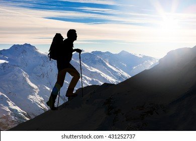 Silhouette Of A Man With Backpack And Hiking On A Mountain