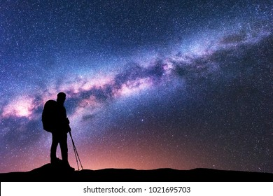 Silhouette of man with backpack and trekking poles against amazing purple Milky Way at night. Space. Landscape with man, bright milky way, sky with stars. Beautiful galaxy. Travel. Starry sky. Nature
