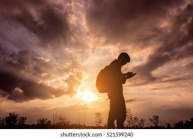 Silhouette man with backpack use smartphone in hands at sunset background, Travel concept.