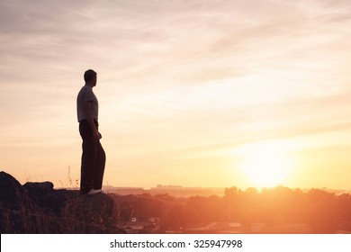 Silhouette of a man at the beautiful sunset on the mountain. Background