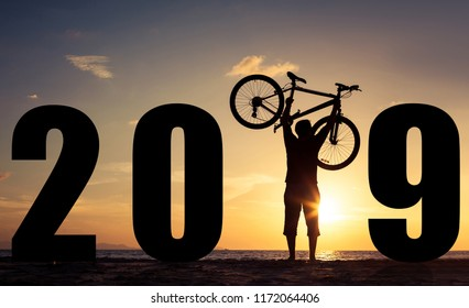 silhouette of a man with a bicycle at sunrise on the sea. Concept of happy new year.
