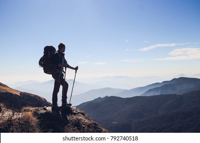 Silhouette of man with big backpack and trekking poles standing on the edge and watching to the distant mountain range in Himalayas