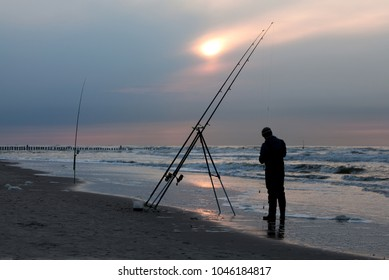 silhouette of a man with big fishing rods on the beach of the north sea island wangerooge, germany in front of dramatic sky while sunset