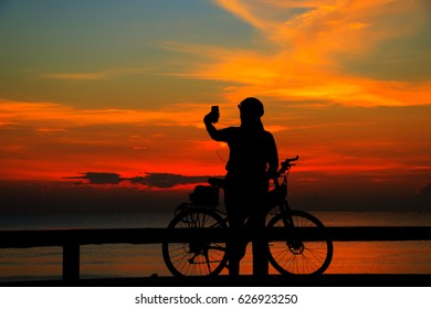 Silhouette man and bike relaxing with sun  effect on sunrise time at beach.