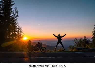 Silhouette of man biker and adventure motorcycle on the road with sunset light background. leap with joy. Top of mountains, tourism motorbike, vacation active lifestyle. Transfagarasan, Romania.