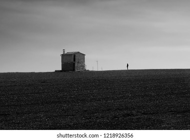 The silhouette of a man in black and white who observes in solitude a small house in the middle of a field in front of the immensity of the flat horizon.