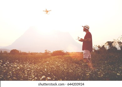 Silhouette of a man blog author is taking photo of a beautiful wild nature on flying go pro camera for his travel web page. Male tourist is shooting video on radio controlled drone during summer trip