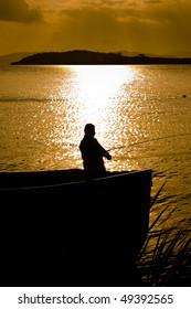 Silhouette of a man in a boat fishing with a beautiful lake background at sunset