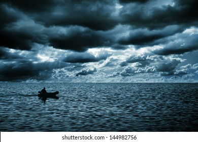 silhouette of a man in a boat floating on the sea. Rich dark clouds. blue tint