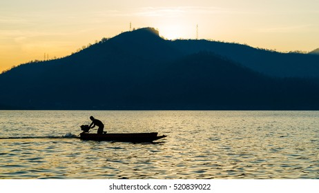 silhouette of a man are boating in the dam on the morning.