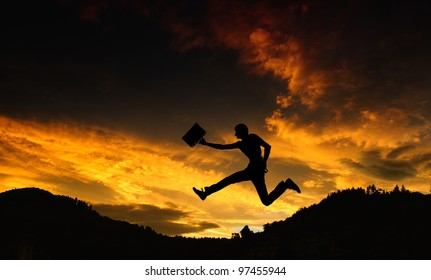 Silhouette of a man with a briefcase - jump at sunset