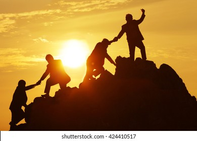 Silhouette of the man Bring hand up a friend to top the peak of mountain on sunrise sky , Business success goal together, Conceptual design.