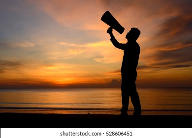 Silhouette man and bullhorn megaphone shout on sunset time