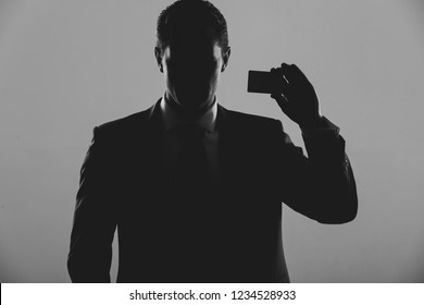 silhouette of man, businessman or manager holding business or bank card in blue formal suit on grey background. Shadow business and economy, banking, fraud, skimming, ecash and information