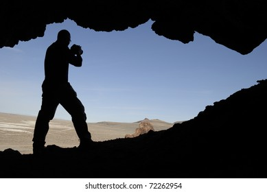 Silhouette of a man with a camera in an opening of a cave shooting out into the Nevada desert.
