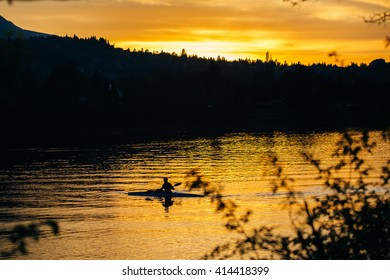 silhouette of a man in a canoe at sunset
