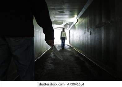 Silhouette of a man carry a knife and follows a young woman in a dark tunnel. Violence against women concept. Real people, copy space