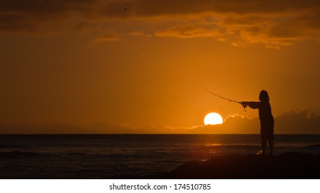 Silhouette of Man Casting a Fishing Rod with Round Orange Setting Sun off the Coast of Honolulu, Hawaii