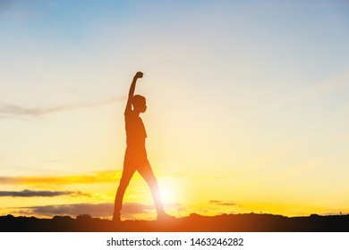 Silhouette of Man Celebration Success Happiness on a mountain top Evening Sky Sunset Background, Sport and active life Concept