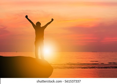 Silhouette of Man Celebration Success Happiness on a Stone Evening Sky Sunset at Beach Background, Sport and active life Concept.