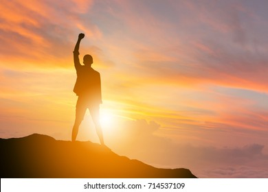 Silhouette of Man Celebration Success Happiness on a mountain top Evening Sky Sunset / sunrise Background, Sport and active life Concept with clipping path